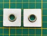 zilverkleurige nestels op wit vierkant van nepleer: gat diameter 8 mm_