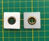 oud-koperkleurige nestels op een lichtgrijs vierkant van nepleer: gat diameter 8 mm_