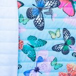 Doorgestikte jassenstof lichtblauw met grote roze en petrolkleurige vlinders