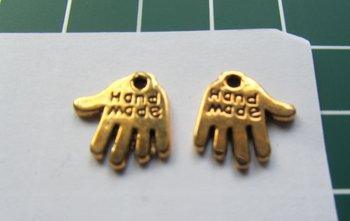 bedeltje: goudkleurig handje met