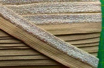 omvouwelastiek 1,6 cm breed met glitterband aan één kant / zandkleur
