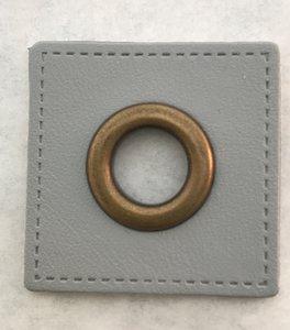 oud-koperkleurige nestels op een lichtgrijs vierkant van nepleer: gat diameter 8 mm